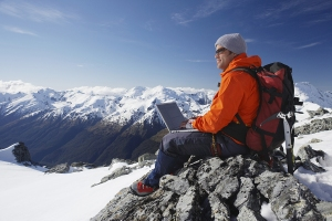 Side view of a male mountain climber using laptop on mountain pe